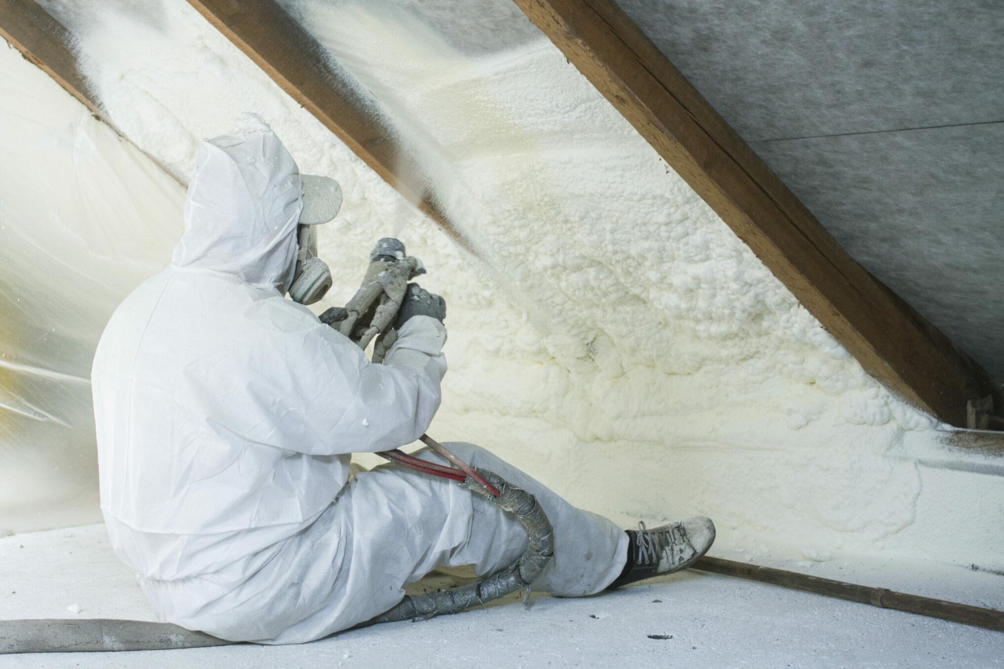 spray polyurethane foam for roof - technician spraying foam insulation using plural component gun for polyurethane foam, inside